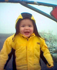 Dylan in a yellow jacket and smiling in the snow on Mt. Diablo