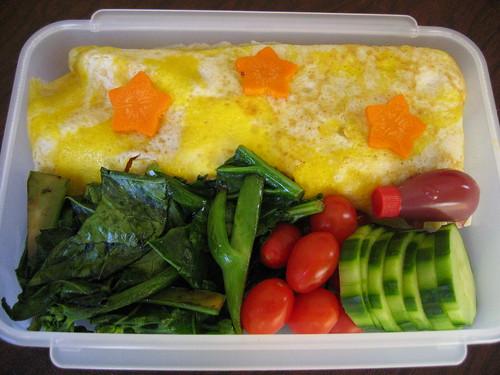 [bento box with omuraisu, sauteed and fresh veggies]