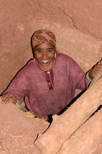 Berber woman on a rustic staircase, Achehoud, Morocco