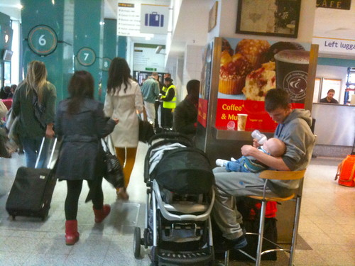 Father feeding baby at train station in London