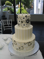 3 tier wedding cake , white ganache ,black & white op art daises, hearts, stripes photo by Charly's Bakery