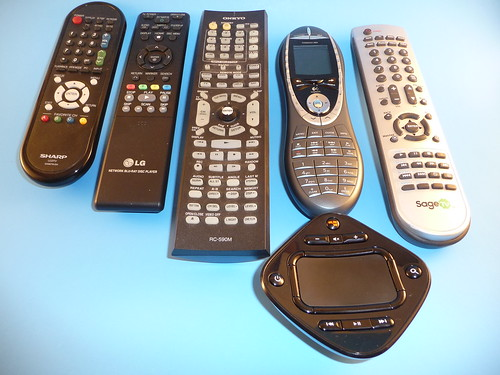 The GlideTV next to Several Remote Controls