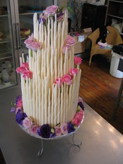 White chocolate cigars wedding cake with lilac, pink & purple flowers photo by Charly's Bakery