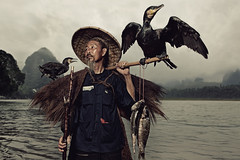 A Chinese fisherman with his two cormorants photo by Glenn Meling