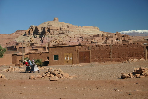 Aït Benhaddou kasbah, snowcapped mountains and berber women carrying firewood