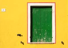 Finestra verde su muro giallo photo by daniele bratovich