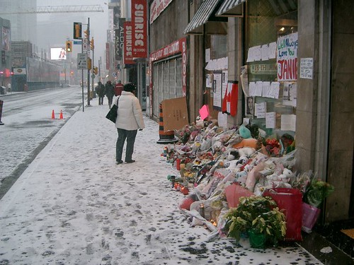 Empty Yonge Street storefront to the left of the Foot Locker store and the makeshift memorial.