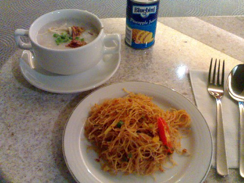 Clockwise from upper left: chicken congee, canned pineapple juice, and fried mee siam