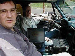 Mike Outmesguine, left, and Frank Keeney of SoCalWUG drive antenna-spiked SUVs equipped with amateur radio equipment, GPS units, and multiple PDAs and laptops running applications such as Netstumbler and Kismet in order to map access points in Los Angeles