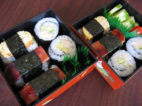 [bento box tiers filled with nigiri sushi and maki sushi]