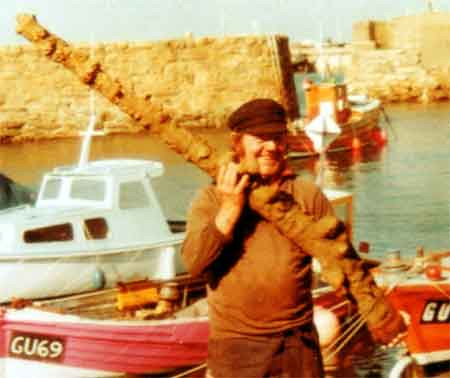 Fisherman Bertie Cosheril with the concreted musket that he found tangled up within his lobster pots. April 1977
