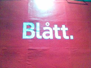 Annonstavla på röd botten med texten 'Blått'