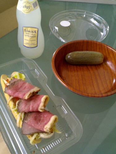A roast beef pickled papaya with marinated grilled artichoke sandwich together with a pickle and lemonade