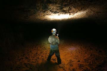Nathaniel Bluedorn in muddy passage in Mushroom Cave