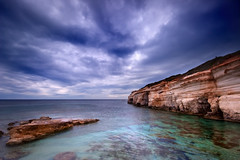 Cloudy sky over rocky coast photo by click cyprus