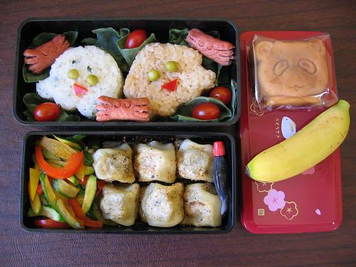 [bento with octopus and squid shaped onigiri, crab hotdogs, dumplings, veggies]