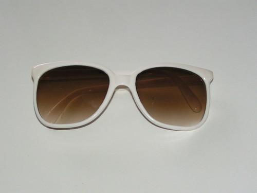 Solglasögon med vita bågar.