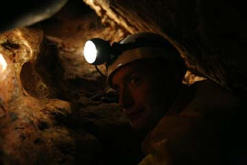 Hans Bluedorn crawling in tight passage in Mushroom Cave