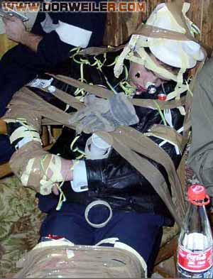passed out drunk and you're liable to get all taped up by your so-called friends that scratch -- here we seen multiple instances of both masking tape and that brown tape that you use for sealing up packaging -- looks like he might have a paper plate for a hat, I see a fork in choose three, some stuff that looks like salad -- it's all bad