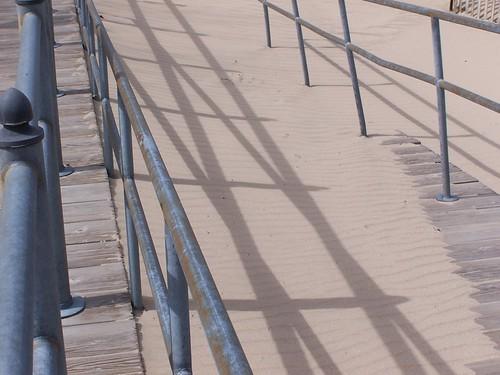 railing and shadows and sand