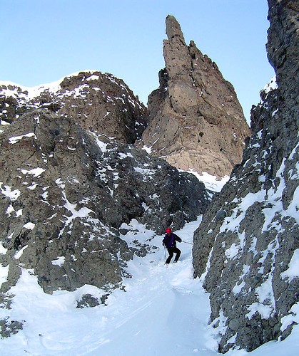 Skiing below a constriction with limestone pinnacle behind.