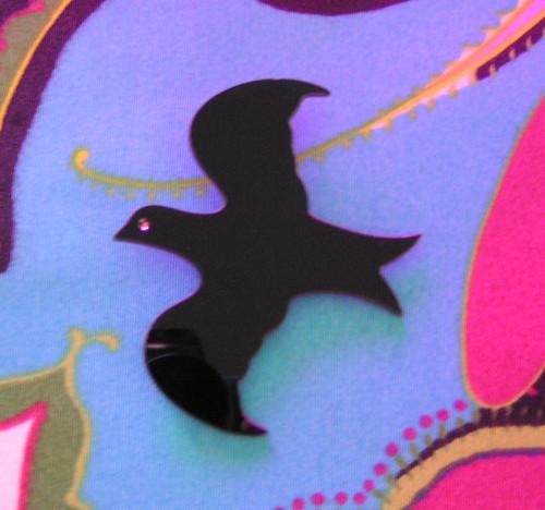Brosch i form av en svart fågel.