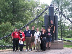A group photo of the participants, standing in front of some old guns