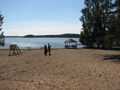 A big sand beach, with a gazebo and a couple of persons standing and talking