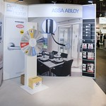 Assa Abloy Home Show Tradeshow stand with competition wheel and Techstyle back wall that has product suspended from it