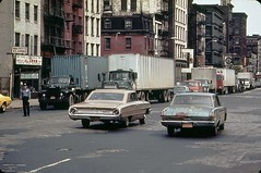 More New York fun from 1973!  A 1960s Ford Galaxie and a battered early 1960s Plymouth Valiant (fixed with bondo) cruise along Canal Street with peeling pavement. The Galaxie has a rope to lock the trunk. New York. photo by wavz13