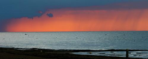 Pluie tombant sur la mer au moment du coucher de soleil