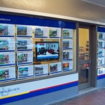 Barfoots Real Estate window display with screen and acrylic pockets suspended using the Fairfield cable and rod system