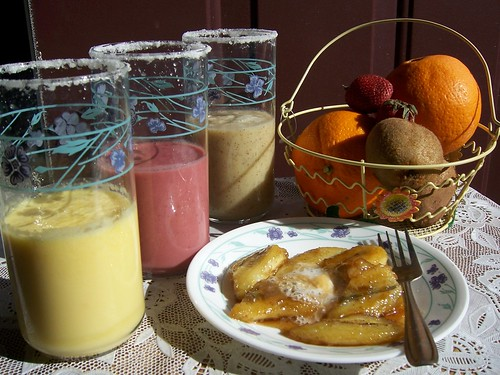 Chilled glasses with Sugar around the rim with Orange,Strawberry,Kiwi Milkshakes  with Plateful of Whipped Creamy Caramalized Banana