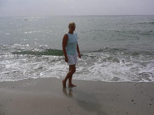 Liselotte med krukket benstilling ved stranden
