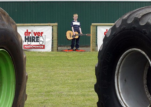 A small boy with a guitar, wearing flippers, is framed between the wheels of two Monster Trucks