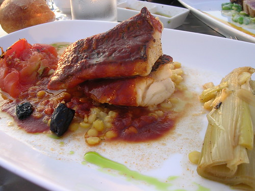 Pan-Seared Black Bass with Saffron Infused Tomato Broth, Yellow Split Peas, Confit Tomato and Braised Leeks
