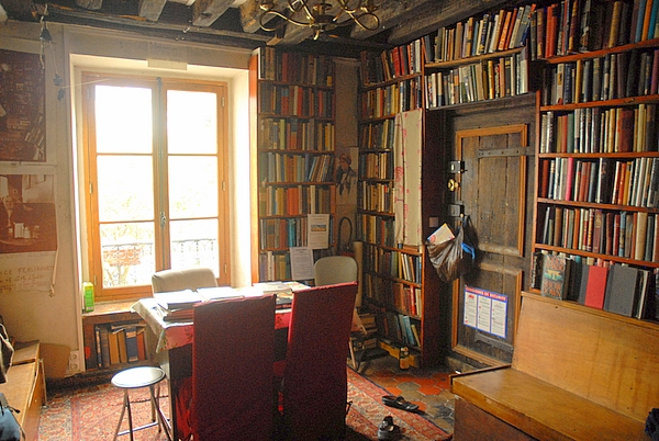 This is the upstairs front library where I sat to read and write while living at the store. Notre Dame iand the Sine River are right out the window. Customers would come in and take pictures of the room.