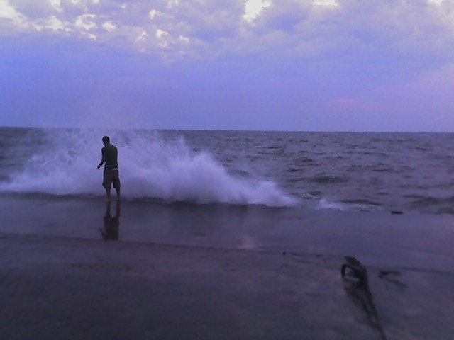dude at the end of the grand haven pier, heavy seas 1