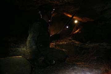 Adam Stanford holding rope prop on ledge in Mushroom Cave