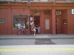 Alex Torres Of The Latin Kings Playing Guitar In Front Of His Music Store.