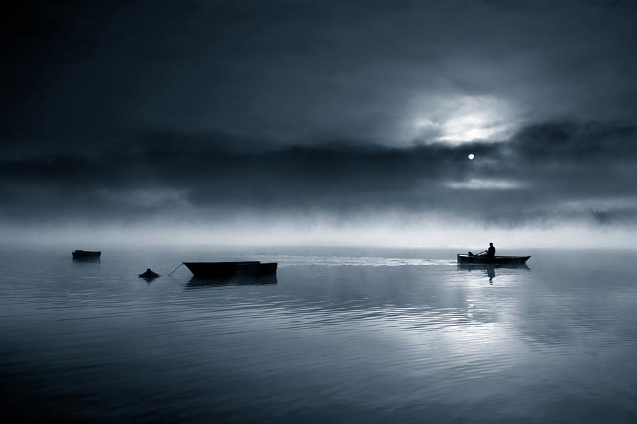 夜晚宁静的湖面,透著月光的云层,还有流连在湖中未离去的船夫或钓鱼客