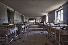 white beds abandoned photo by Jonathan Aubry
