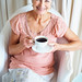Smiling senior woman drinking coffee while reading newspaper