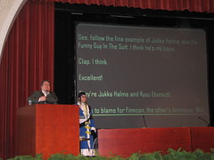 Jukkahoo behind the podium, Kyuu Eturautti standing beside it; funny translations on the screen in the back