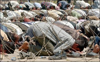 Un grupo de musulmanes realiza uno de sus rezos junto a una valla de pinchos colocada por los marines durante la invasión de Bagdad, en abril de 2003.