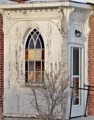 Old wooden side entrance; stained-glass window