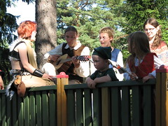 Guests sitting on a pirate ship, singing and playing a guitar