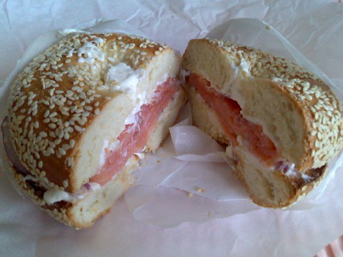 A sesame bagel toasted with cream cheese, lox, and onions