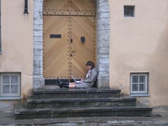 woman on a laptop in centuries-old doorway in Estonia