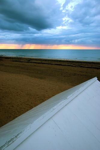 Toit d'une cabine de plage et pluie tombant au loin